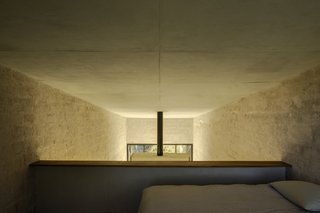 The loft bedroom is located beneath the highest point of the roof and overlooks the sitting area below.