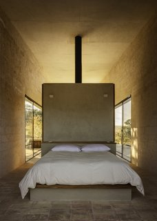 Clay tile floors and timber surfaces tie the building to the land. The locally quarried stone walls are left exposed in the interior.