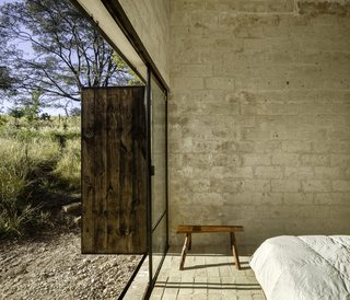 Sliding glazed doors open the ground-floor bedroom up to the outdoors. The timber bench was locally crafted.