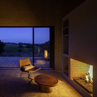 The wood-burning hearth fills the home with an orange glow at night.
