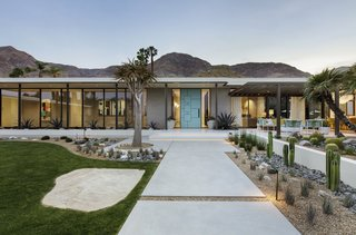 Poured concrete walkways flanked by desert landscaping lead to the architect-designed front door painted bright blue.
