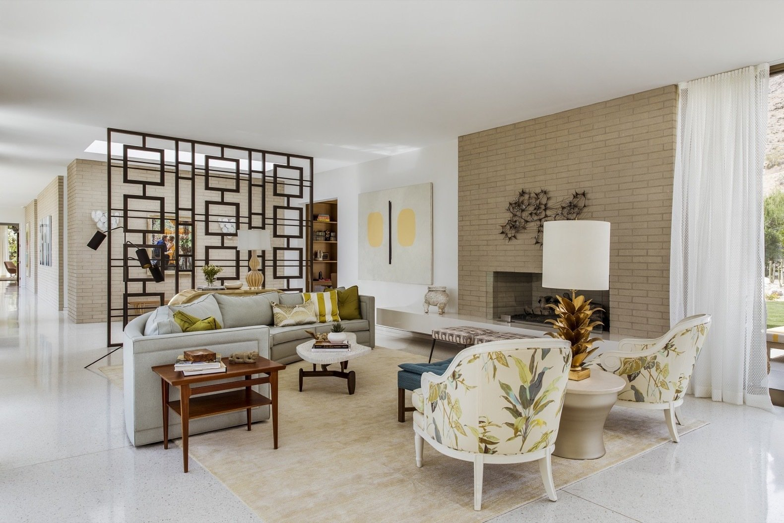 Living Room, Terrazzo Floor, Chair, Table Lighting, Coffee Tables, Gas Burning Fireplace, and Sofa The living room features a double-sided gas fireplace, a pair of Jan Showers chairs, a 1stdibs coffee table, a custom Kush Rugs rug, and a Look Modern teak side table.