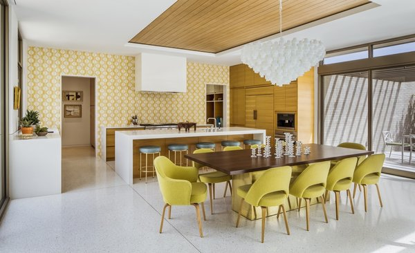 Yellow Popham Design tiles add whimsy to the kitchen. A vintage Murano glass chandelier hangs above a custom table surrounded by DWR chairs.