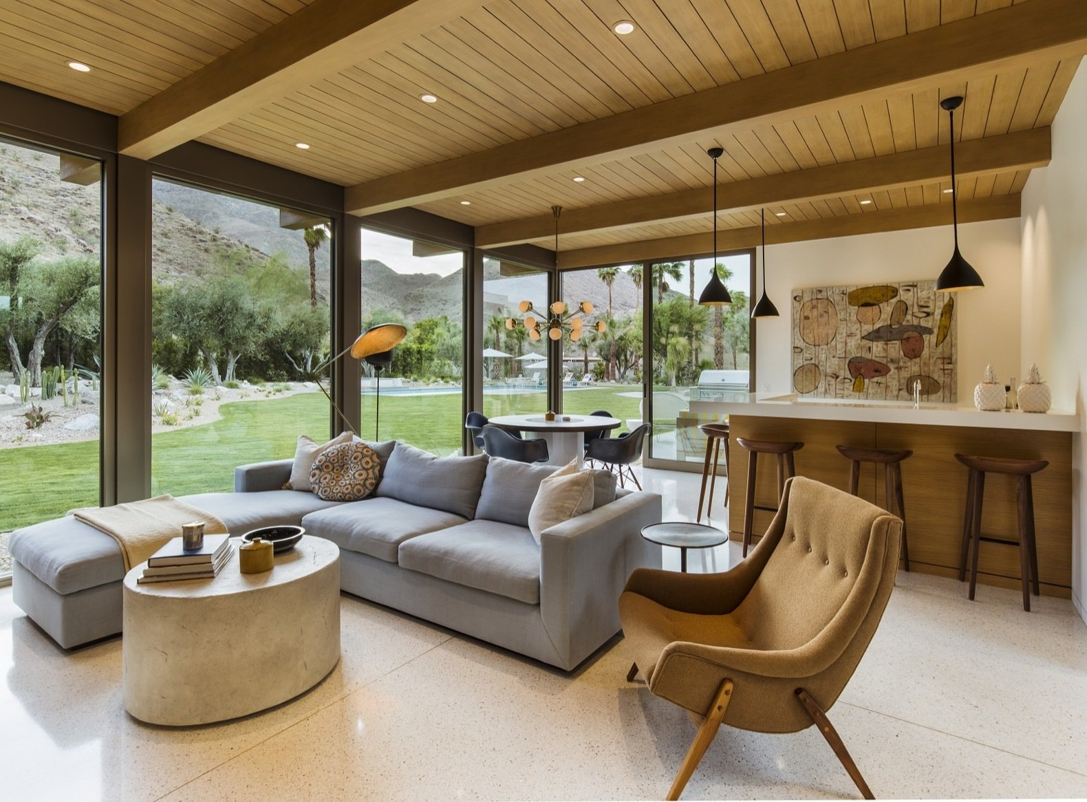Living Room, Pendant Lighting, Chair, Coffee Tables, Sectional, Terrazzo Floor, and Recessed Lighting Located across the entrance, the cozy family room includes a mini bar and overlooks the outdoor patio and backyard with the relocated pool.