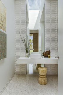 Bathed in daylight, the powder room includes Heath Ceramics wall tile and a custom slab vanity and mirror.