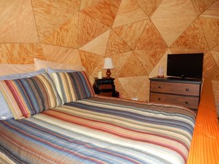 """Underneath the """"mushroom cap"""" geodesic dome is a loft bedroom with a queen-sized Casper mattress as well as a 32"""" flat-screen TV."""