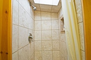 A peek inside the travertine shower, which is illuminated by a skylight.