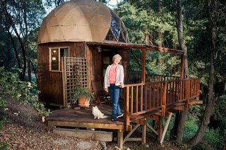 Kitty Mrache stands in front of the Mushroom Dome Cabin, which continues to hold the title as Airbnb's most popular rental, as confirmed in Airbnb's press release celebrating the company's milestone for half a billion guest arrivals.