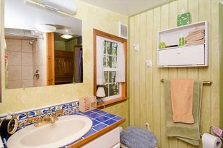The custom-tiled sink adds a pop of color and personality to the compact bathroom. In the corner is a Nature's Head composting toilet.