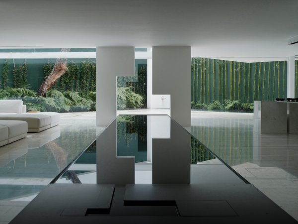 Leading to a lush wall of green, the long reflecting pool on the ground floor divides the space, with the living area on the left and the dining area on the right.