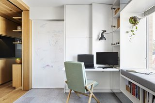 The sliding door separating the living room from the bedroom can be used as a whiteboard. The Hybrid Chair from Studio Lorier can be converted from an office chair (seen here) to a lounge chair.