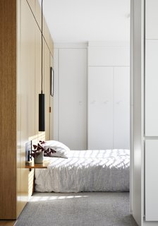 Bathed in light from the rising sun, the bedroom includes a wall of built-in closets. The nightstand is a fold-down wall panel.