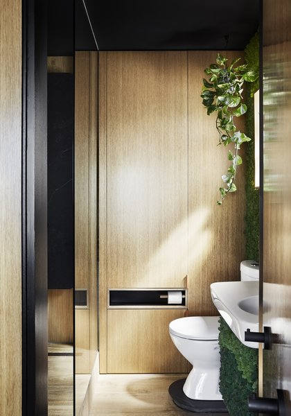 """I really enjoy the bathroom space, as the apartment doesn't have an outdoor space so I tried to create the illusion of green outdoor environment in the bathroom, with the green moss wall, timber tiles, etc.,"" says Chen. The bathroom, seen here from the bedroom, also has a retractable clothesline."