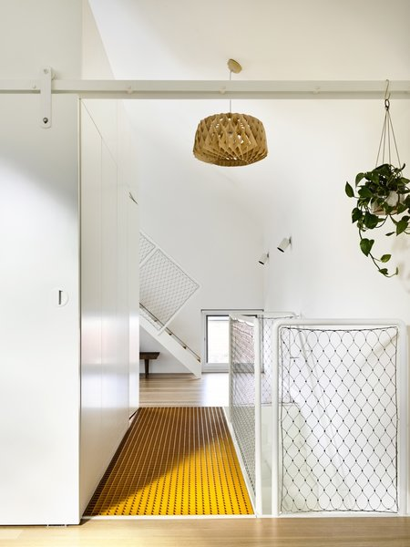 """The playful aesthetics of Austin Maynard Architects have once again breathed new life into aging building stock—this time with the transformation of a dark and narrow terrace in Melbourne into an open and light-filled home fitted out with sustainable features. Upstairs, the """"parents' retreat"""" includes a centrally located bathroom """"box,"""" seen on the left of the image. The bright orange walkway is perforated to let natural light pass through."""
