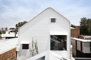 The architects designed an asymmetrical roof so as to avoid shading the neighbors' backyard. Note how the window awnings appear to peel up and away from the facade.