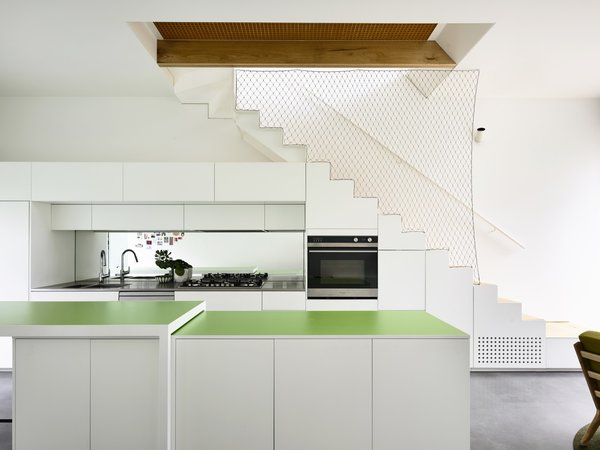 Juicy Green Laminex island countertops add a bright pop of color to the all-white kitchen. The rear countertops are stainless steel, and the backsplash is mirrored glass.