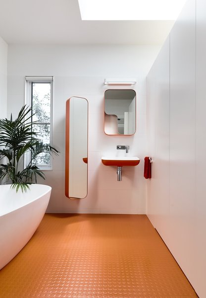"A skylight illuminates the master bathroom, which is entirely outfitted with Arblu Tulip fixtures. The orange floor is Kenbrock K2 studded rubber. Note how the divisional wall stops short of the ceiling—a decision that the architects implemented to ""create volume and height, which celebrate the curve of the ceiling."""