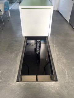 Part of the kitchen island slides back to reveal the hidden entrance to the cellar. For added protection, a perforated steel sheet can be used to cover the opening.