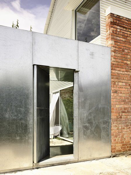 Built of galvanized steel, the new front door conveys safety and security. The owners had previously experienced a break-in, and they thought a more imposing entrance could serve as a deterrent. Directly behind the entry is the courtyard linking the old and new buildings.