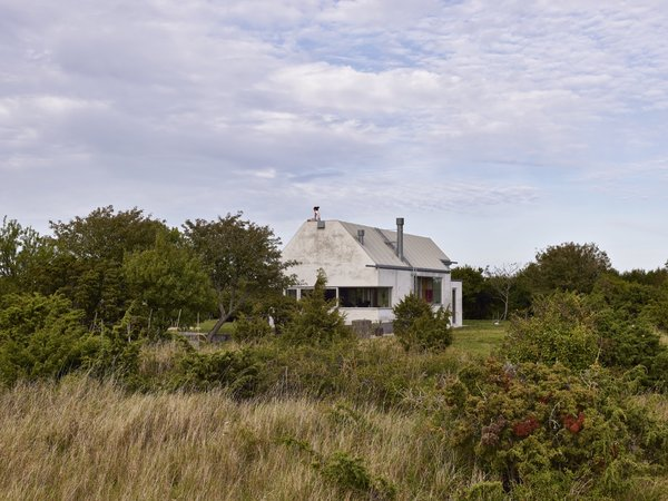 """Located on the Swedish island of Gotland, the house is designed to look like a large boulder to blend in with the landscape. """"It is a stone among other stones,"""" the designers say."""