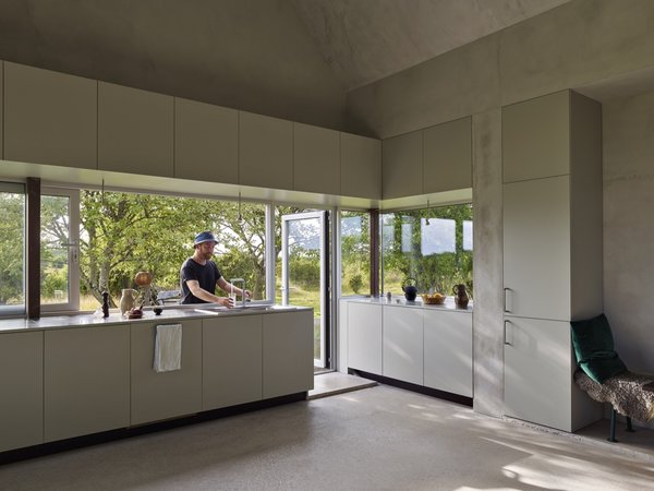 Concrete Floor In the summer, the kitchen counter transforms into an indoor/outdoor kitchen island. The outdoor dining room is located between two whitebeam trees.  Photo 5 of 16 in A Brilliant Little Home Wins Sweden's Most Prestigious Architecture Award