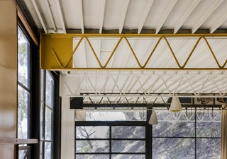 The exposed web joists were painted different colors, while the ribbed underside ceiling of the Ferrobord roof decking was painted white.
