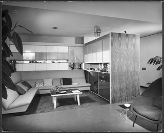 This photo from 1950 shows the living room alcove with a custom built-in sofa, cupboards, and cabinetry.