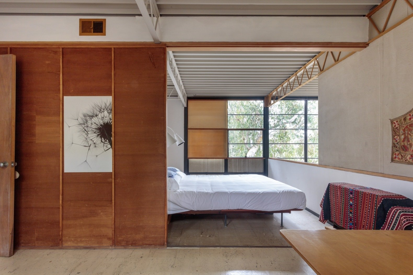 A view into the master bedroom as seen from the guest bedroom. When open, the sliding wood panel combines both bedrooms into one large space.  Photo 17 of 21 in Getty Unveils New Plan to Conserve the Iconic Eames House