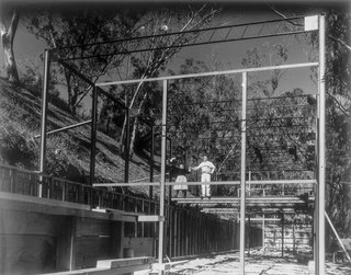 Ray and Charles Eames seen standing on the steel frame of the house, which consist of two rows of 4-inch H-columns set 20 feet apart. A 12-inch open-web joist forms the top member.