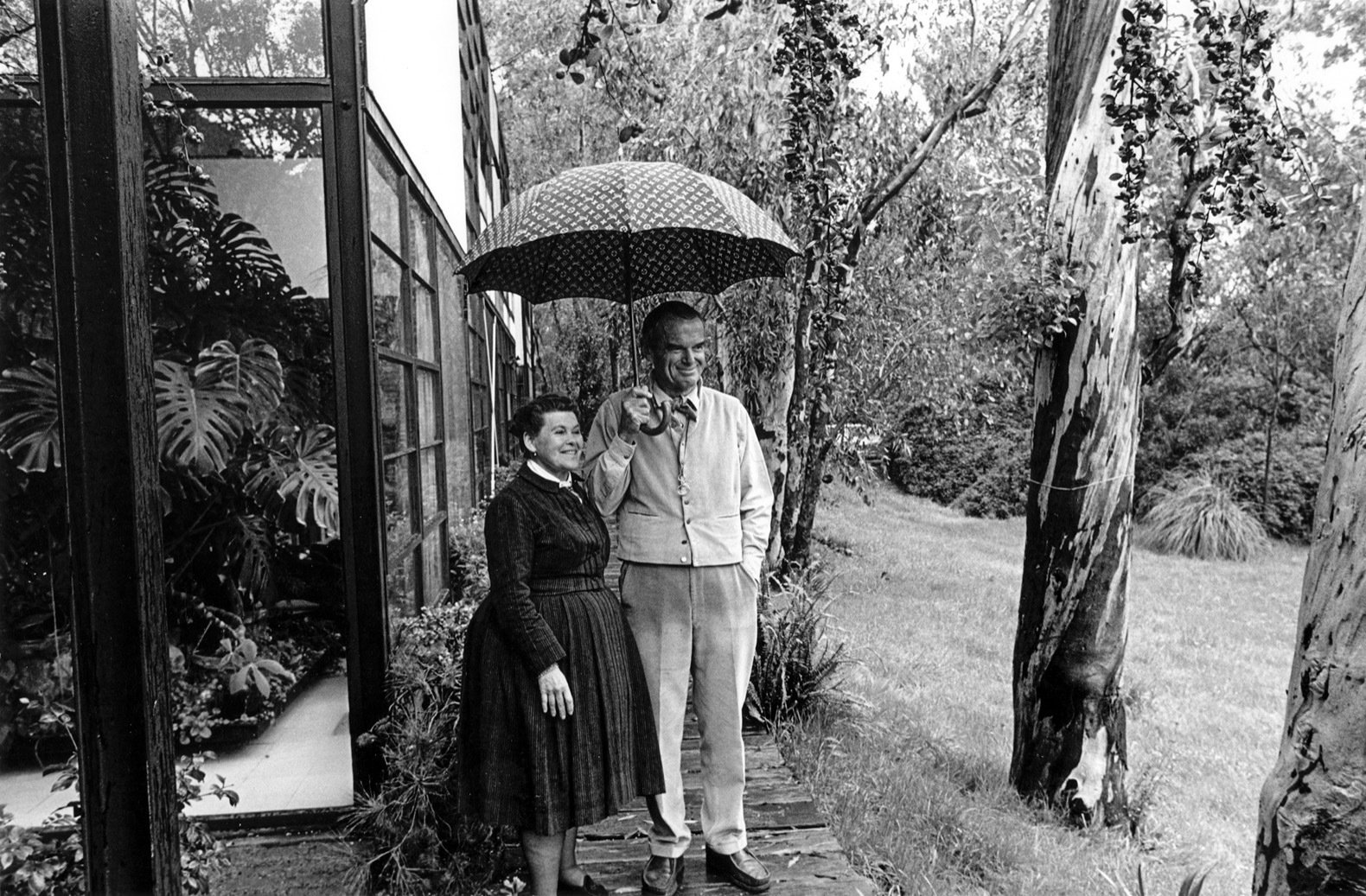 Ray and Charles standing beneath an umbrella next to historic eucalyptus row that dates back to the 1880s and is still standing today.