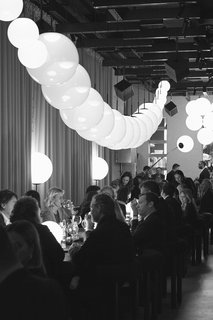 Design week guests dine under Opal pendant lamps arranged like a string of translucent pearls.