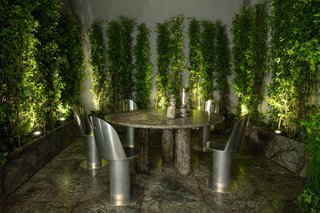 Set in the center of The Manzoni is a courtyard with a custom-made, forest-green marble table designed by Testi and JKL Design Studio flanked by lush greenery on three sides. The aluminum chairs are by Shapes.
