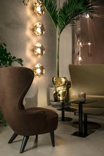 Cut surface lights in gold illuminate new Flash tables in black and a Wingback sofa and chair.