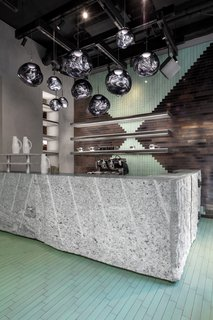 The entrance features a bar made from monolithic granite offcuts. The rough-cut granite is complemented by sleek lava stone tiles and Opal lights.