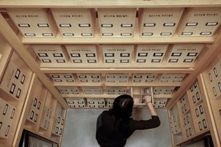 The products are stored in natural wood boxes that live in a glass-walled, humidor-style display case.