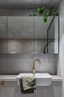 Located behind the kitchen beneath the mezzanine, the bathroom makes up for its lack of natural light with bright lights and mirrored cabinets that create the illusion of spaciousness.