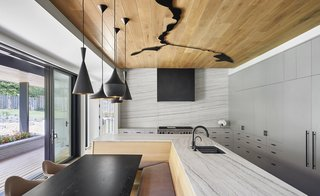 The kitchen features a white oak-paneled ceiling with a powder-coated steel sculpture of the stream. The backsplash and countertops are White Macaubus Marble with streaks that bring to mind the movement of water.