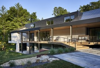 Topped with a custom-made steel roof, the home is wrapped in glass and painted brick.