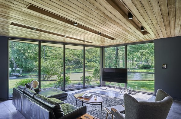 """The """"Man Cave,"""" or lower lounge, opens up to the outdoors through full-height glazing. The chair and ottoman seen in the corner is by Modernica."""
