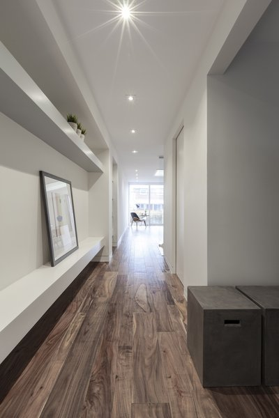 Acacia Natural planks line the floors and are complemented by white walls. Pictured here is the entry hall to the open-plan living, dining, and kitchen area.