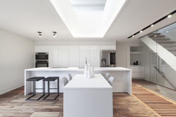 For a clean and bright finish, the light-filled kitchen is fitted with white quartz countertops and high-gloss white IKEA cabinetry.