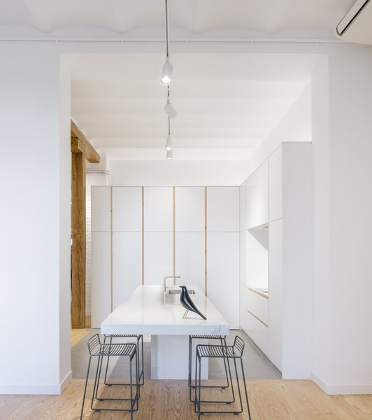 Drawing inspiration from Japanese contemporary architecture, Jorge Alonso Albendea of Zooco Estudio gave this home in Madrid a modern and minimalist aesthetic. The kitchen features a waxed concrete floor and Muji-esque cabinets, lighting, and counters.