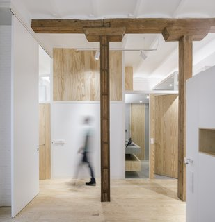 Wooden surfaces—from the bathroom door to the screen that provides privacy to the upper bedroom—complement the existing pine floor and exposed timber structure.