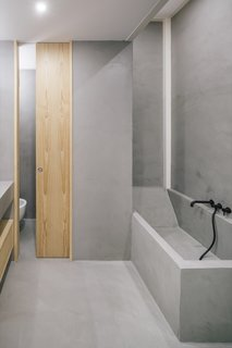 A sliding pocket door to the toilet saves space and contributes to the bathroom's streamlined look.