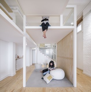 Above the lounge is a casual work studio with a desk surface that's suspended from the ceiling.