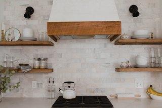 An Italian marble backsplash complements the open shelving made from reclaimed wood purchased from local Amish shops.