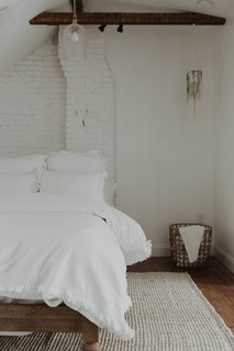 The designers painted the exposed brick in the attic white to match the walls and bedding, and also restored the original hardwood floors.