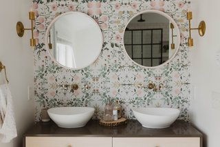 To complete the boho feel, the designers added an Urban Outfitters wallpaper behind the double vanity. The handmade brass fixtures are from Pepe & Carols.