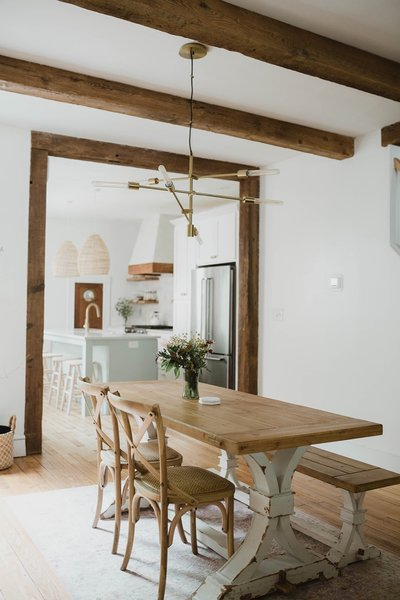 Chris and Claude Beiler tore down the wall that divided the kitchen and dining room. A West Elm light fixture hangs over the dining table; reclaimed timber ceiling beams and trim lend a sense of warmth to the interior.