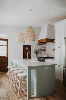 A local cabinet shop custom-made the island, which includes a built-in dishwasher. One of Chris and Claude's favorite additions to the house is the back pantry door, which once belonged to a ship. The designers had stored the little wooden door for years, waiting for the perfect opportunity to use it.